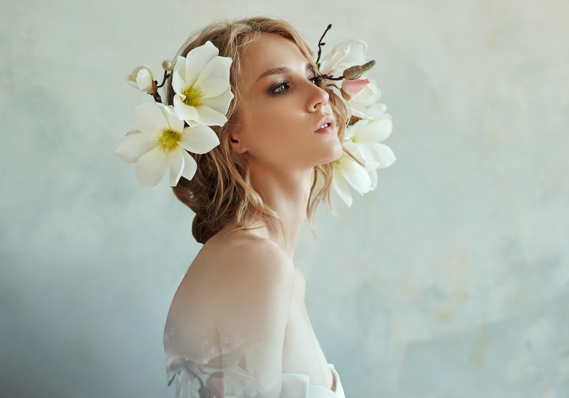 Art Girl blonde flowers near the face. Natural cosmetics for skin care, woman and natural beauty of the skin. Hydration and rejuvenation, anti-wrinkle agent
